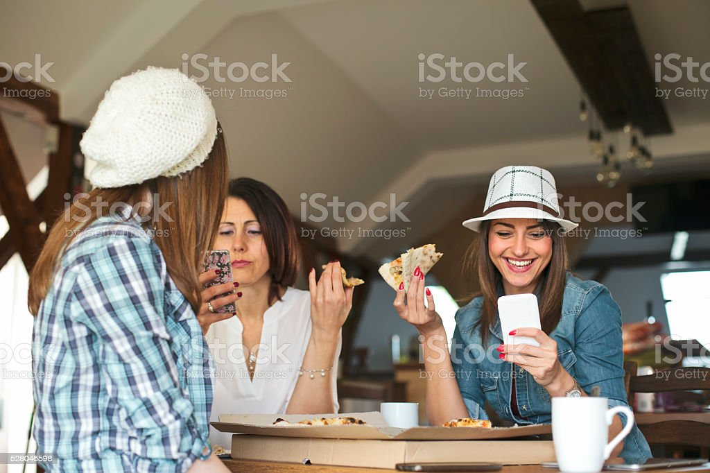 female friends sharing a pizza stock photo