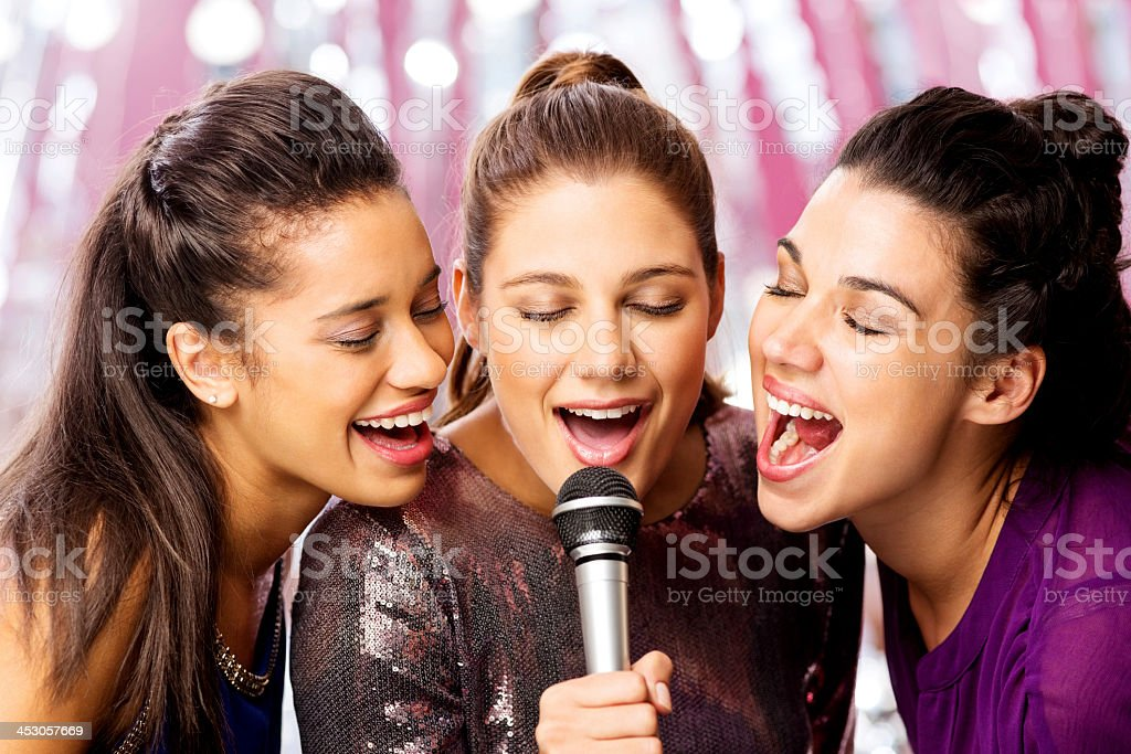Female Friends Singing Karaoke Into Microphone At Nightclub stock photo