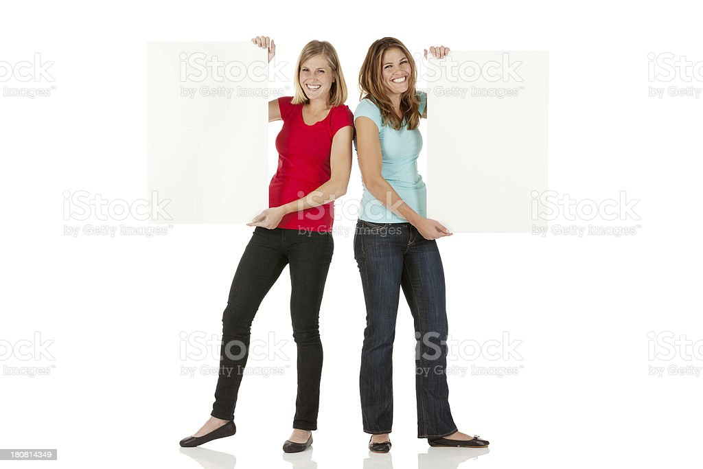 Female friends standing with placards royalty-free stock photo