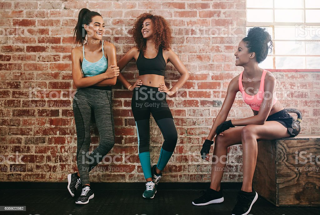 Female friends taking rest after fitness workout stock photo