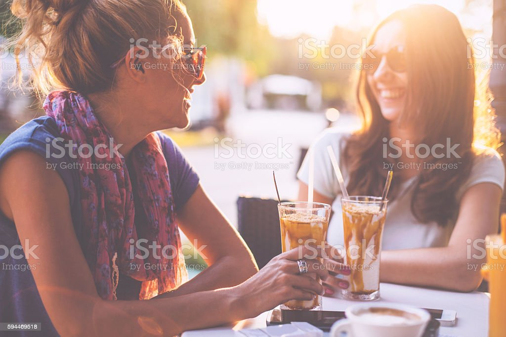 Female friends talking in cafe stock photo