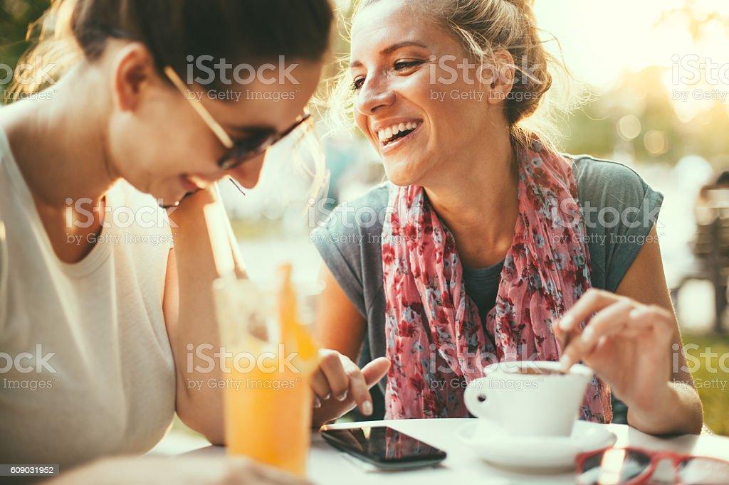 Female friends talking in cafe stock photo