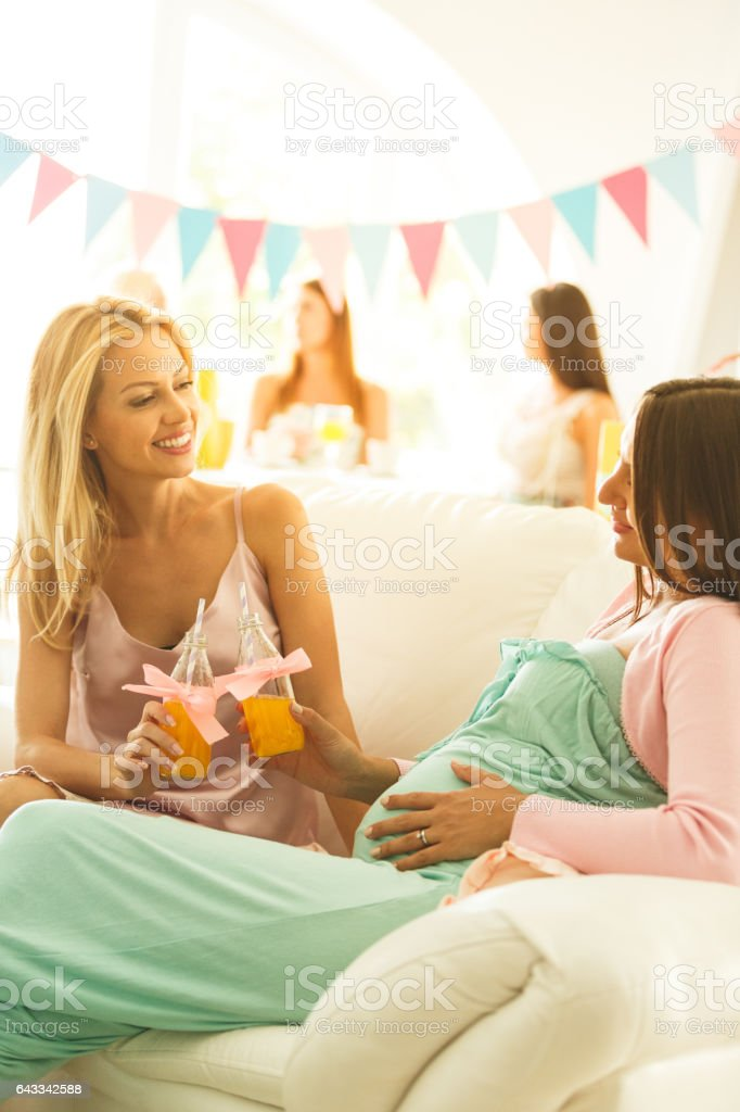 Female friends toasting at baby shower stock photo