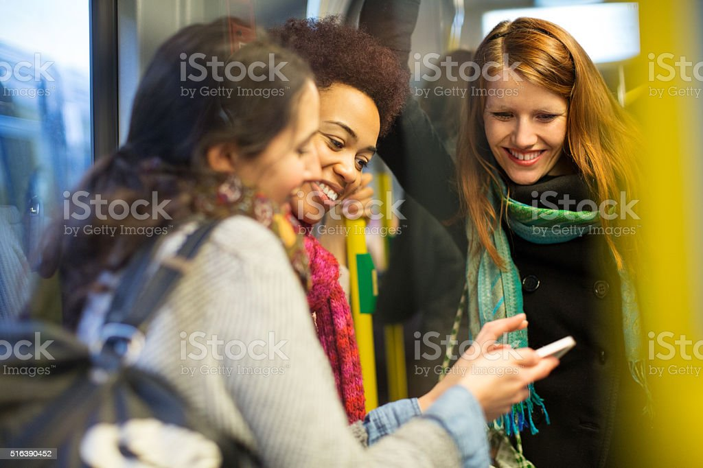 Female friends traveling by train using mobile phone stock photo