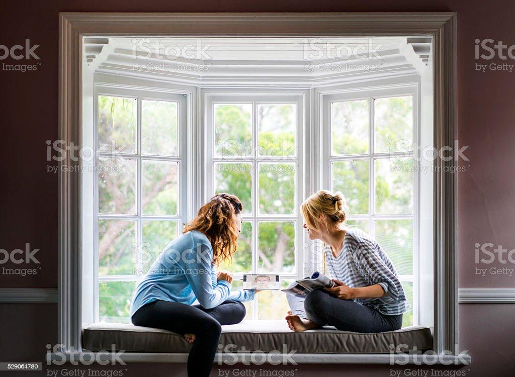 Female friends using digital tablet on window sill stock photo
