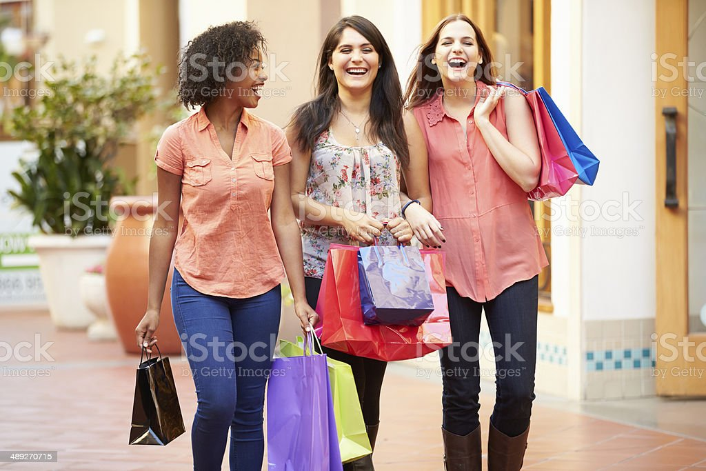 Female Friends Walking Through Mall With Shopping Bags royalty-free stock photo