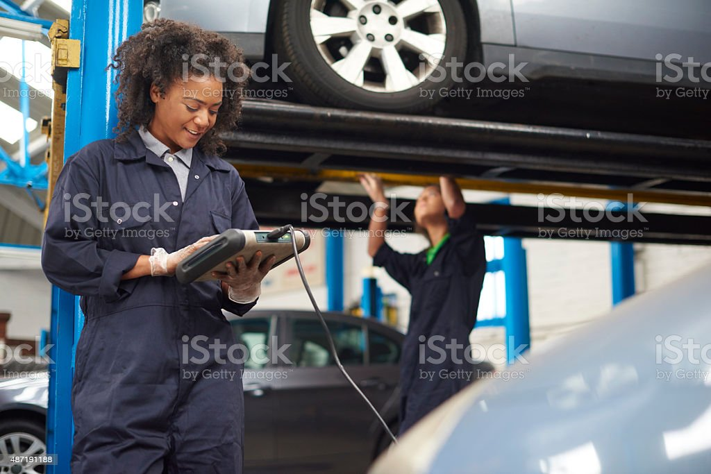 female garage mechanic conducting diagnostic check. stock photo