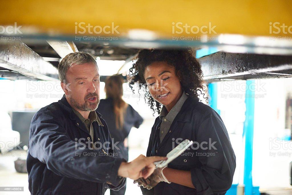 Female garage mechanic with her boss stock photo