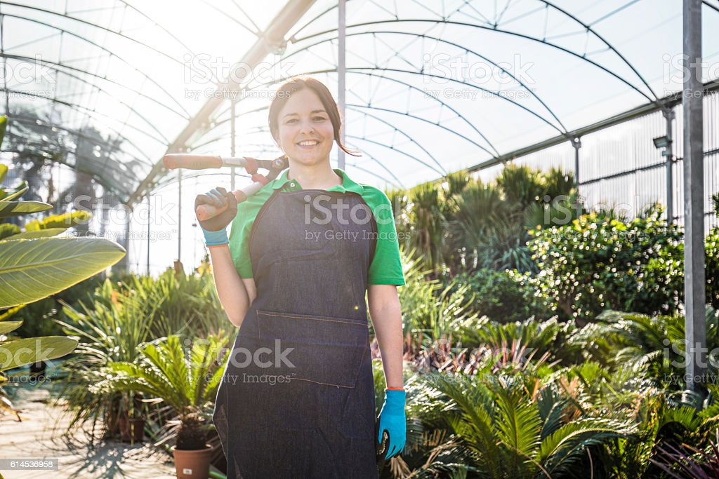 Female garden center worker with tools stock photo