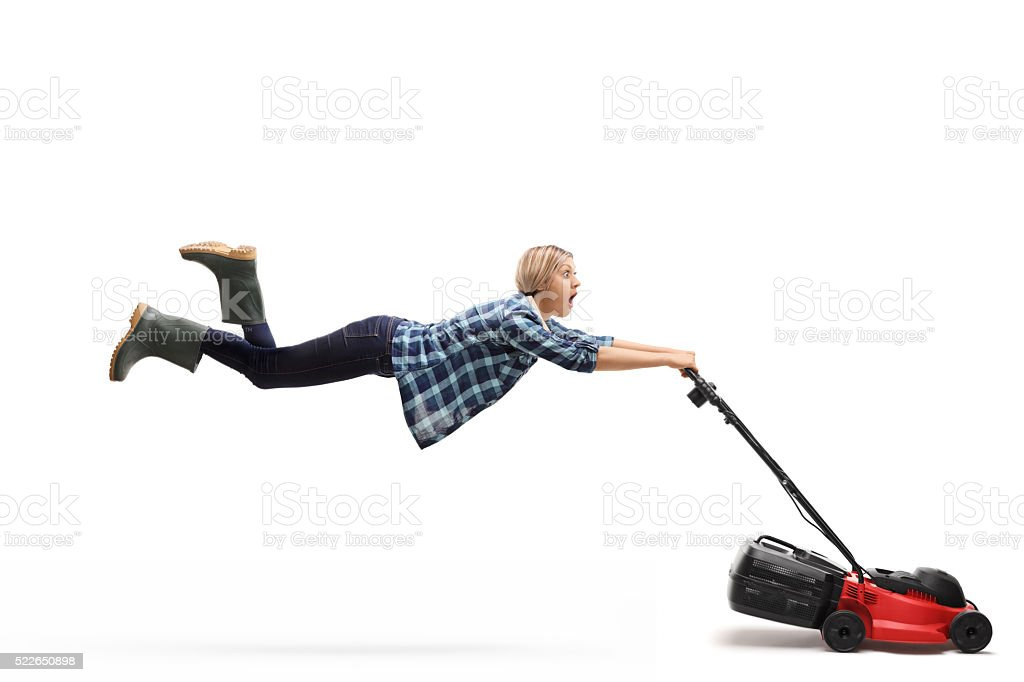 Female gardener being pulled by a lawnmower stock photo