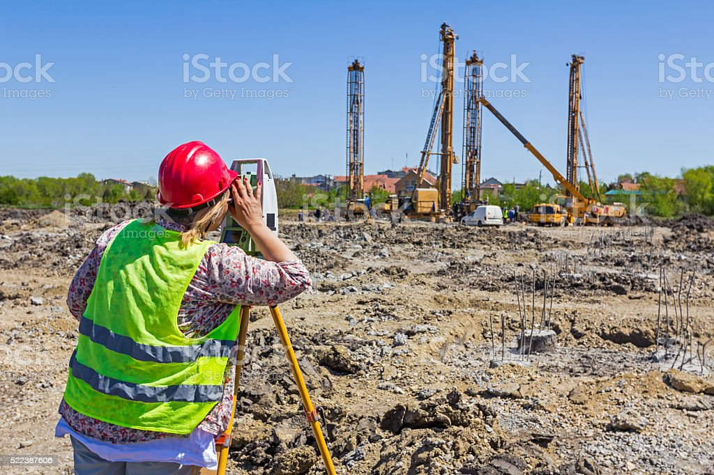 Female geodesist is working with total station on  building site stock photo