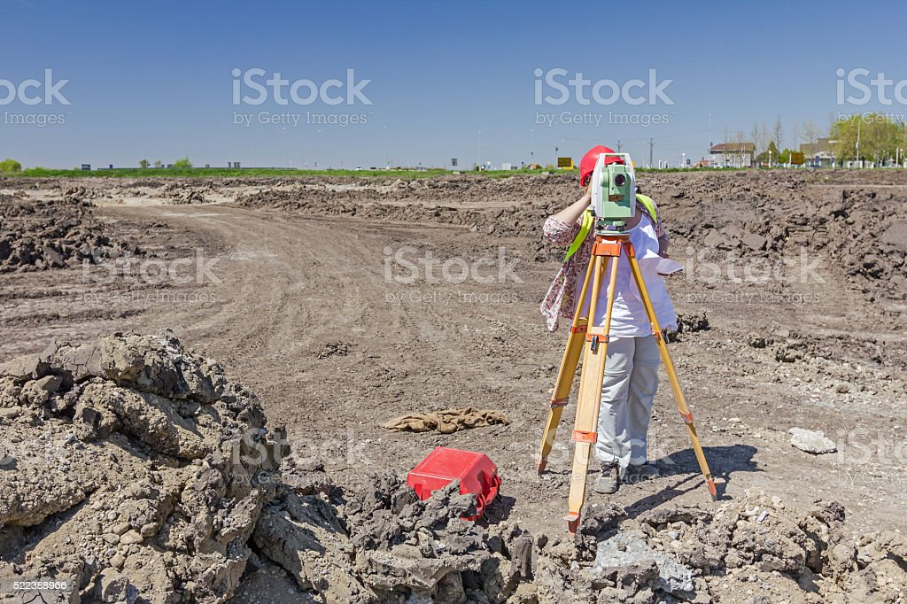 Female geodesist is working with total station on building site. stock photo