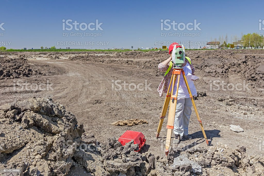 Female geodesist is working with total station. stock photo