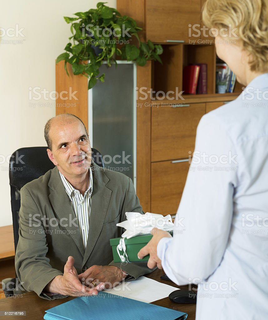 Female giving present to male colleague stock photo