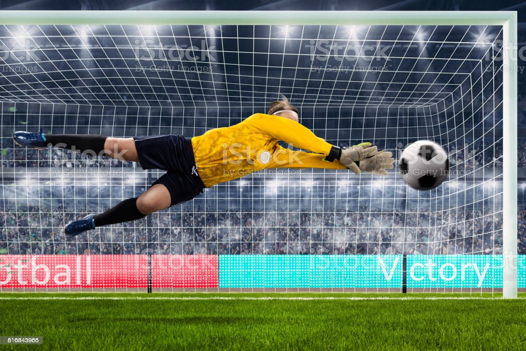 female goalie is jumping for the ball on crowded stadium stock photo