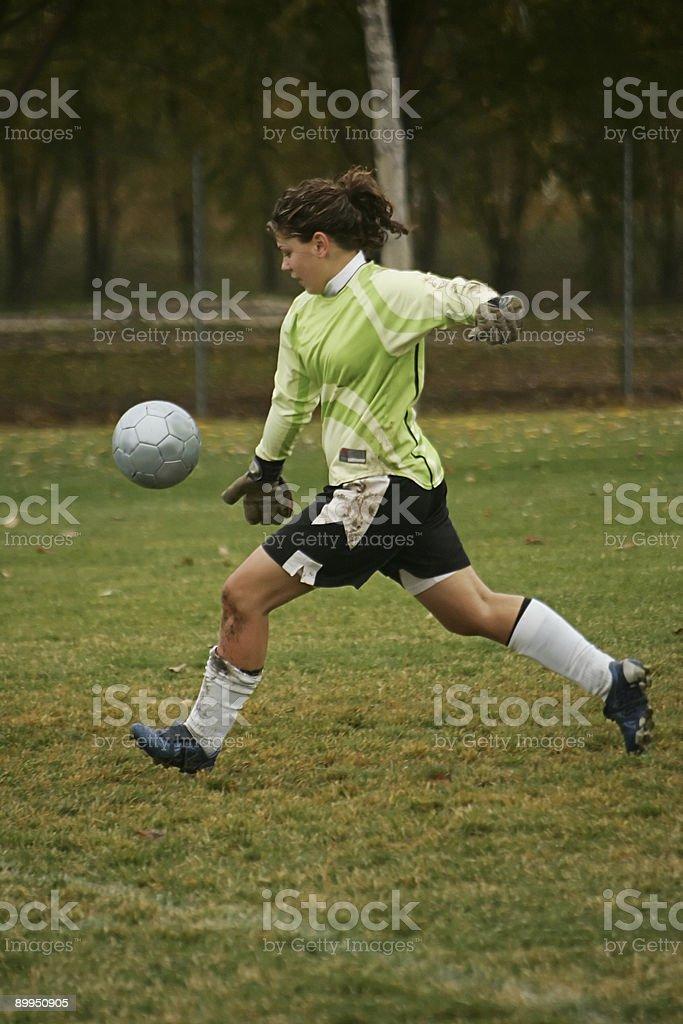 Female Goalkeeper in Green Agressively Drop-Kicks Ball royalty-free stock photo