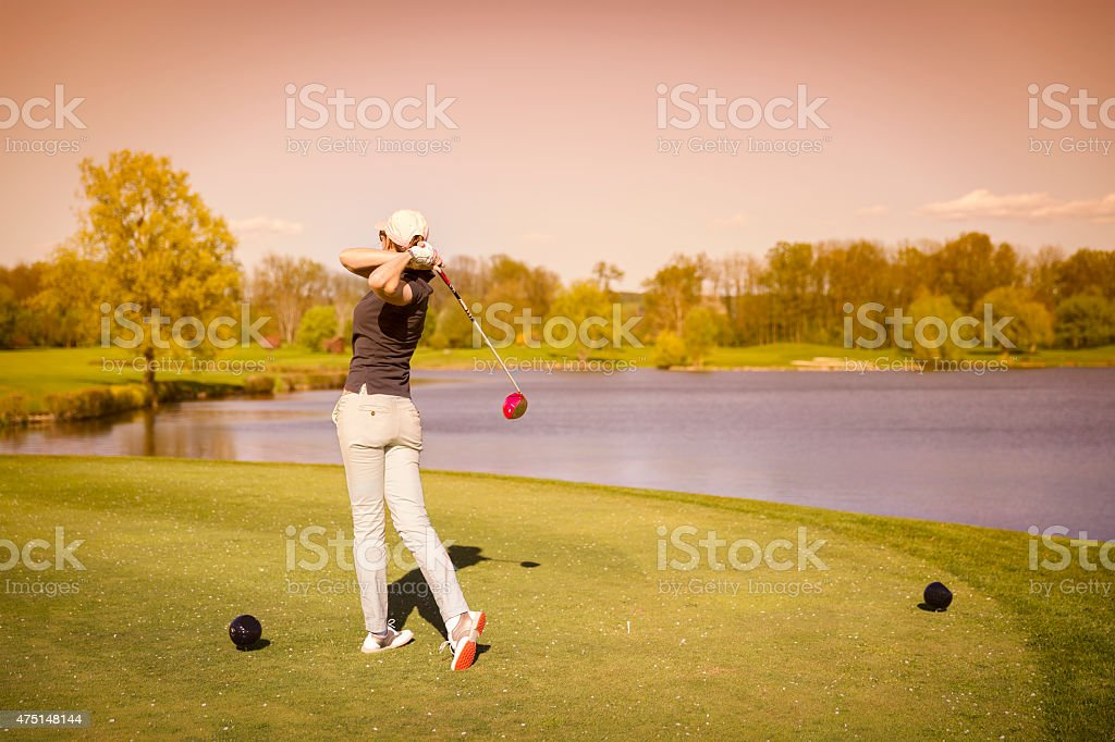 Female golf player teeing off. stock photo