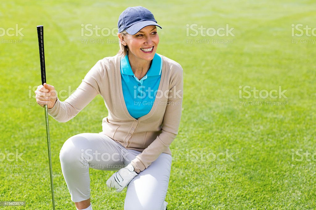 Female golfer kneeing on the putting green stock photo