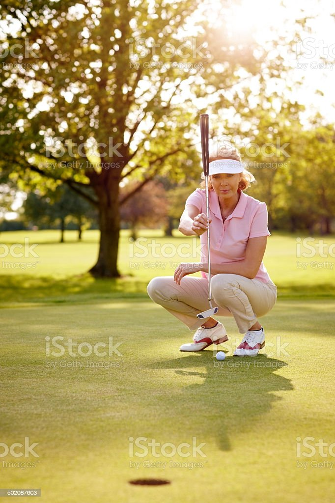 Female golfer lining up for her shot stock photo