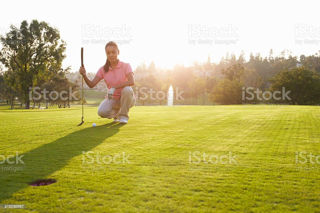 Female Golfer Lining Up Putt On Green stock photo