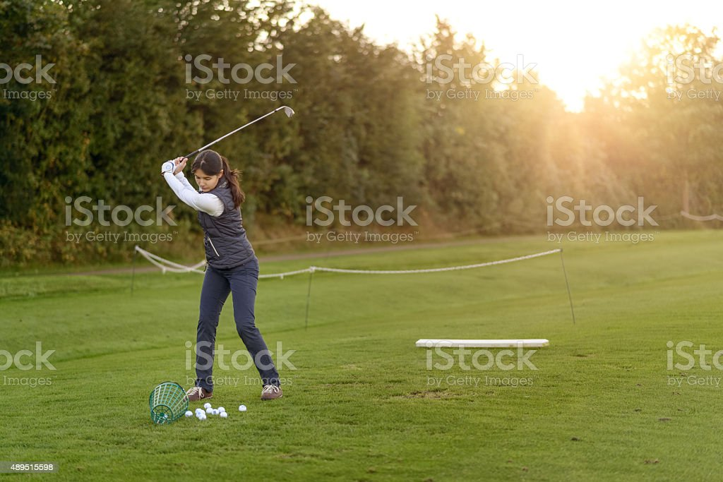Female golfer practicing on a driving range stock photo