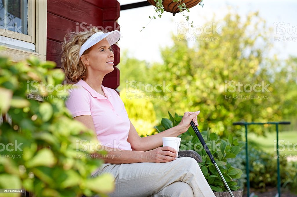 Female golfer resting after a game stock photo