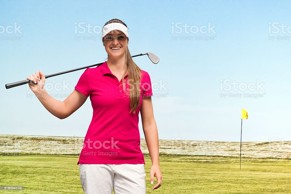 Female golfer standing in field stock photo