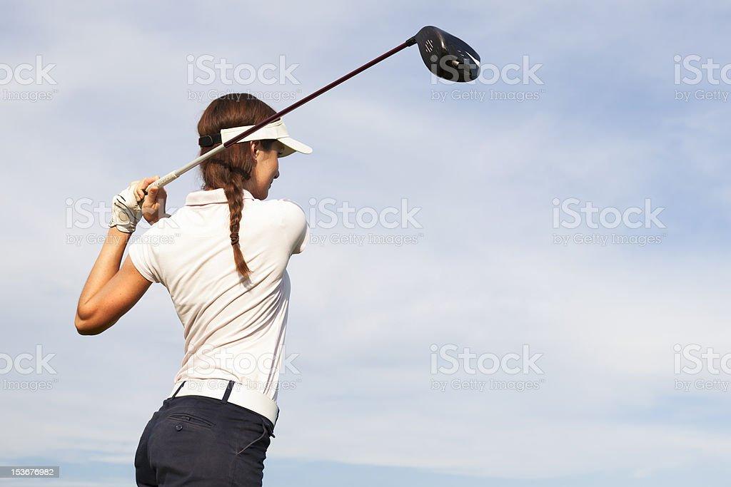 Female golfer swinging golf club behind head royalty-free stock photo
