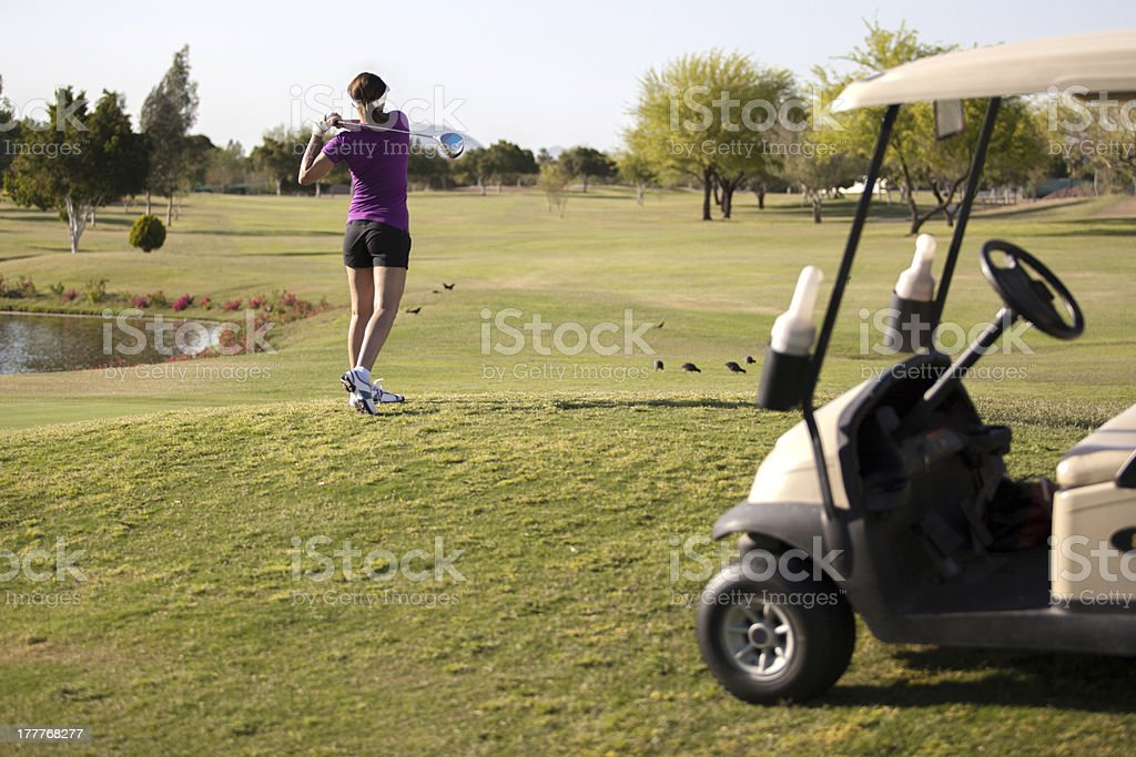 Female golfer teeing off royalty-free stock photo