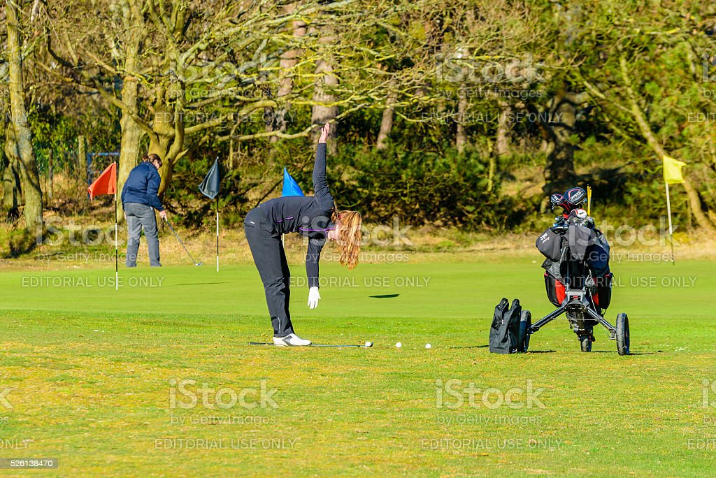 Female golfer warm up stock photo