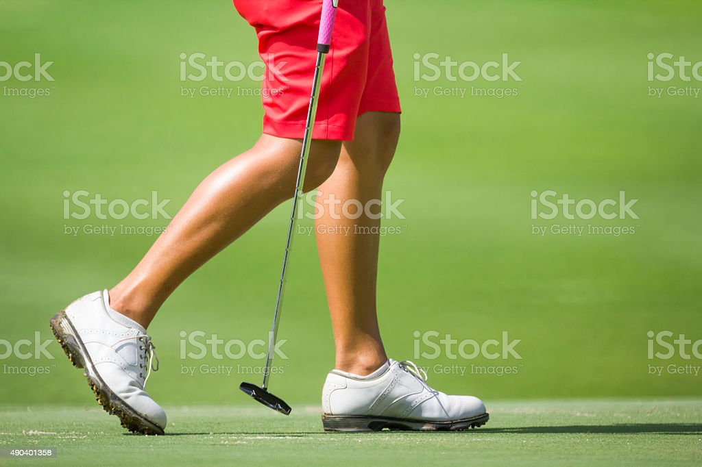 Female golfers walking on green with putter. stock photo
