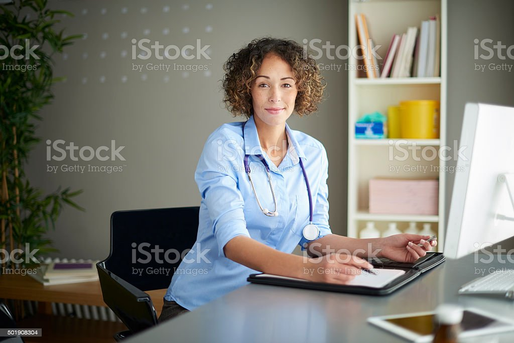 female gp sitting at her desk stock photo