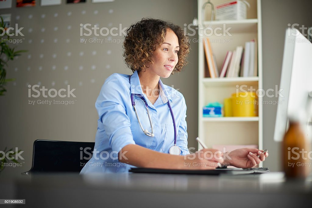 female gp sitting at her desk stock photo