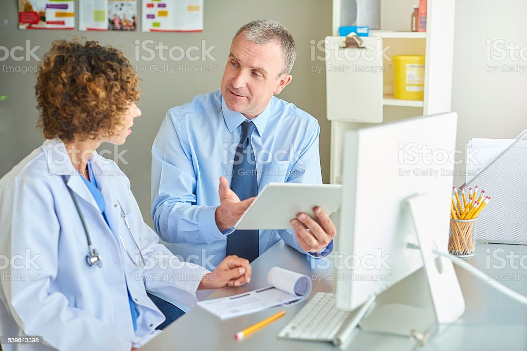 female gp with administrator stock photo