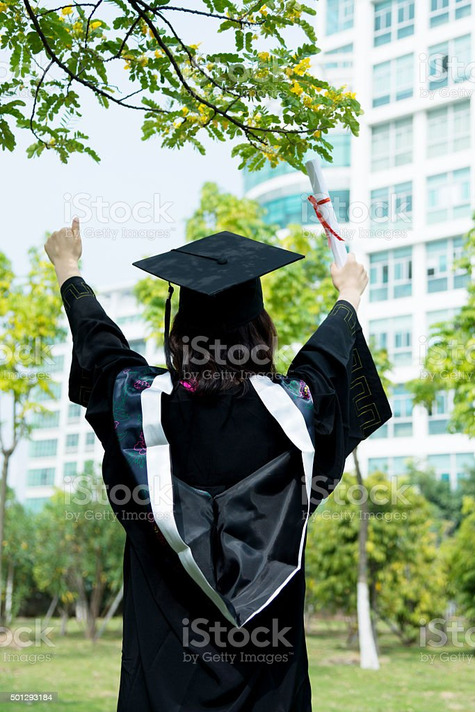 Female graduate student with hands raised stock photo