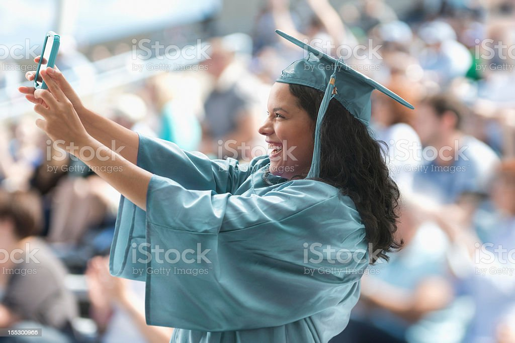 Female graduate taking photograph of herself royalty-free stock photo