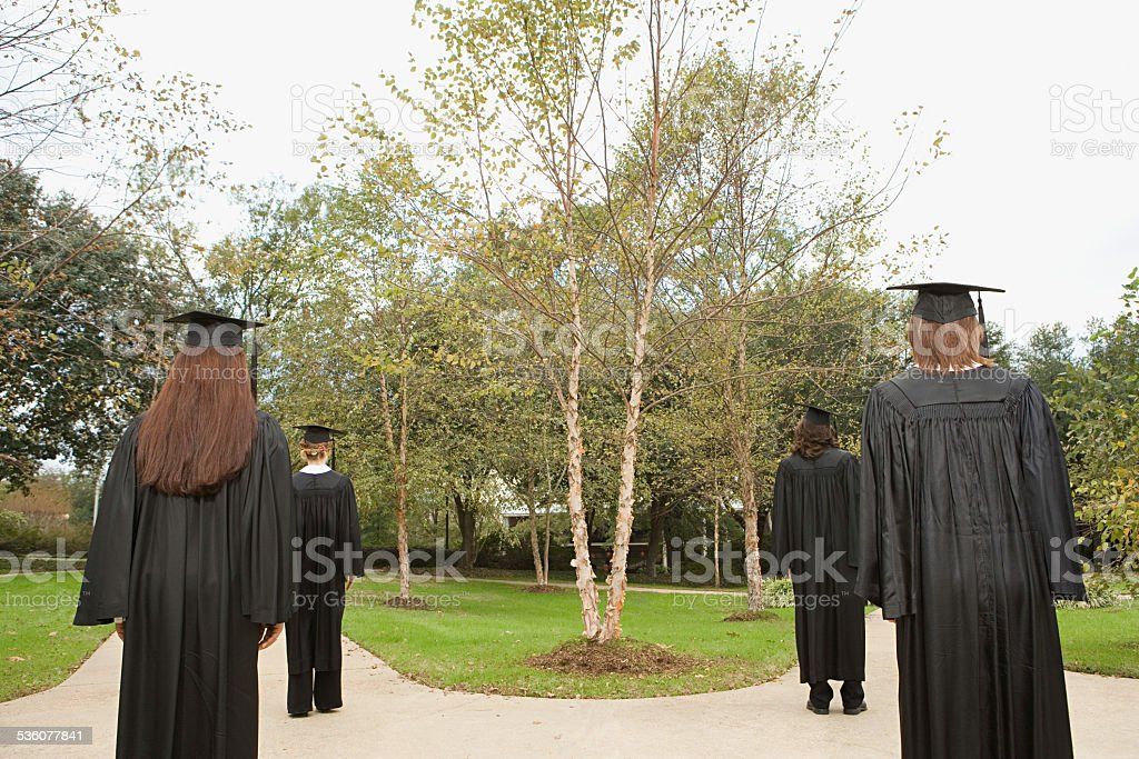 Female graduates walking down paths stock photo