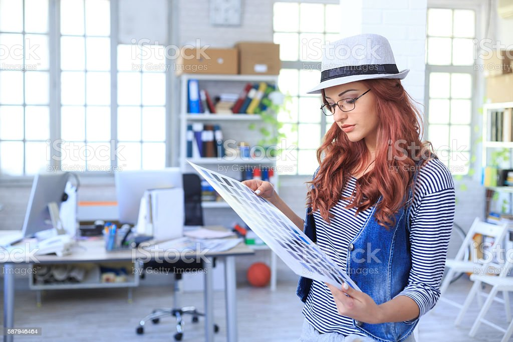 Female graphic designer looking at color schemes stock photo