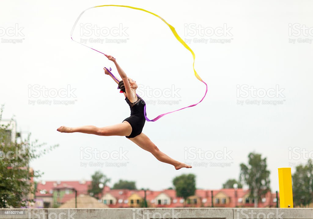 Female Gymnast Dancing Outdoors With Ribbon stock photo