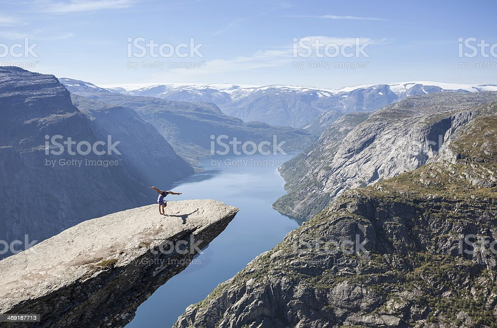 female gymnast doing a handstand on trolltunga rock in norway stock photo