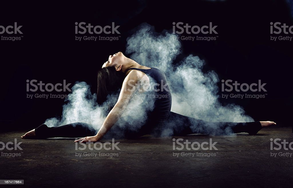 Female gymnast doing splits engulfed by smoke royalty-free stock photo
