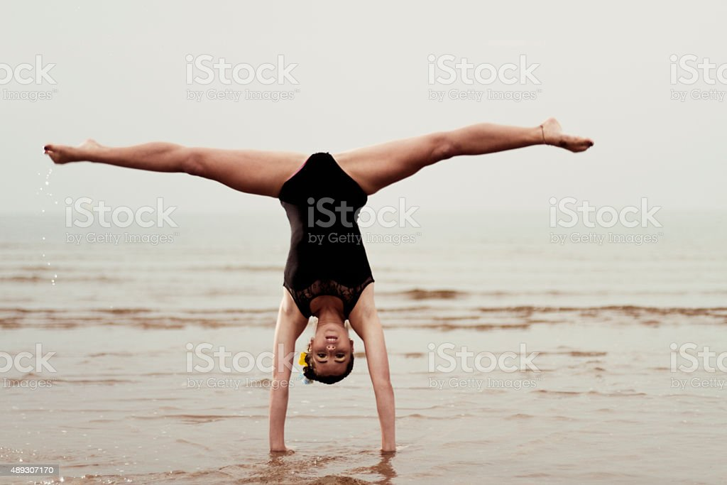 Female gymnast exercising at the seaside stock photo