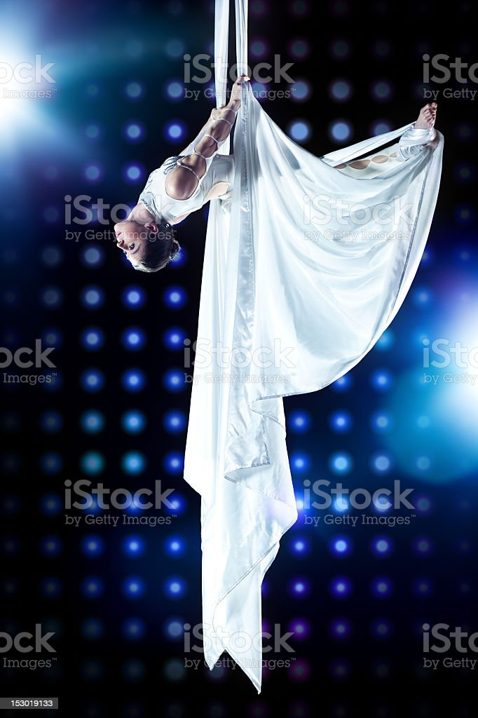 Female gymnast hanging from the ceiling using aerial fabric stock photo