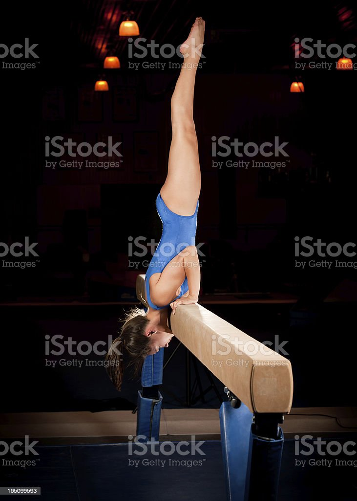 Female Gymnast In Handstand On  Balance Beam Routine stock photo