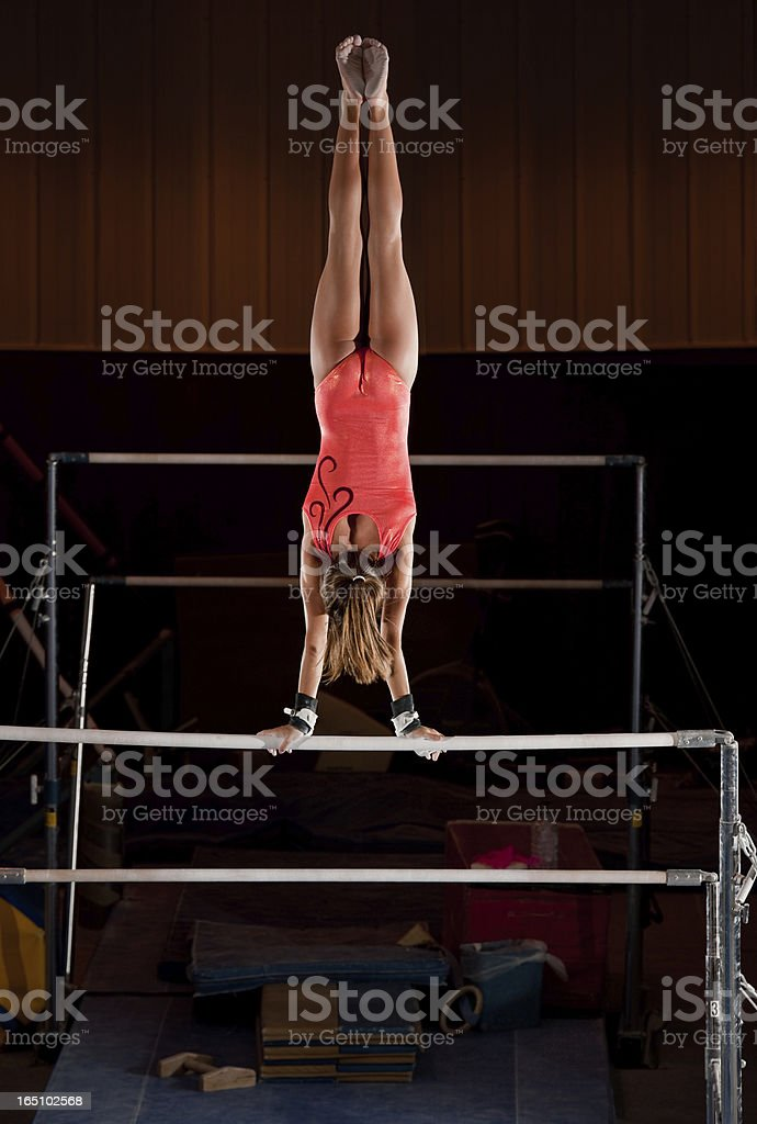 Female Gymnast In Handstand Top On Uneven Bars royalty-free stock photo