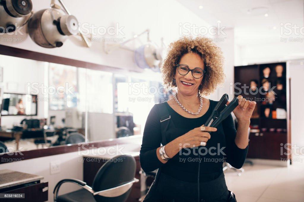 Female hairdresser at the salon holding a hair straightener stock photo