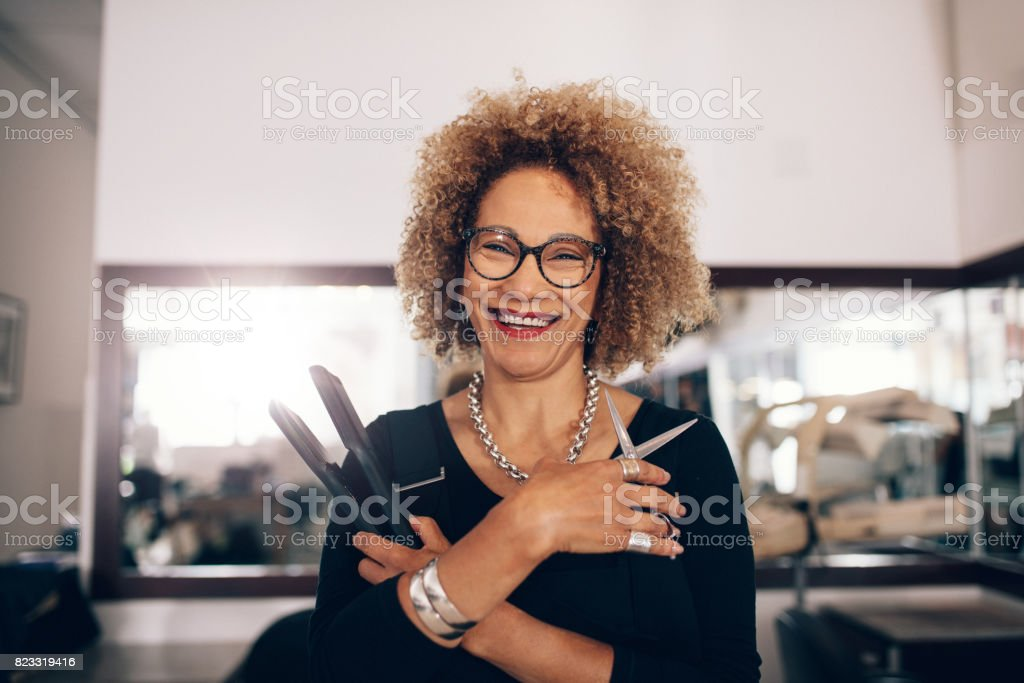 Female hairdresser at the salon holding hairdressing accessories stock photo