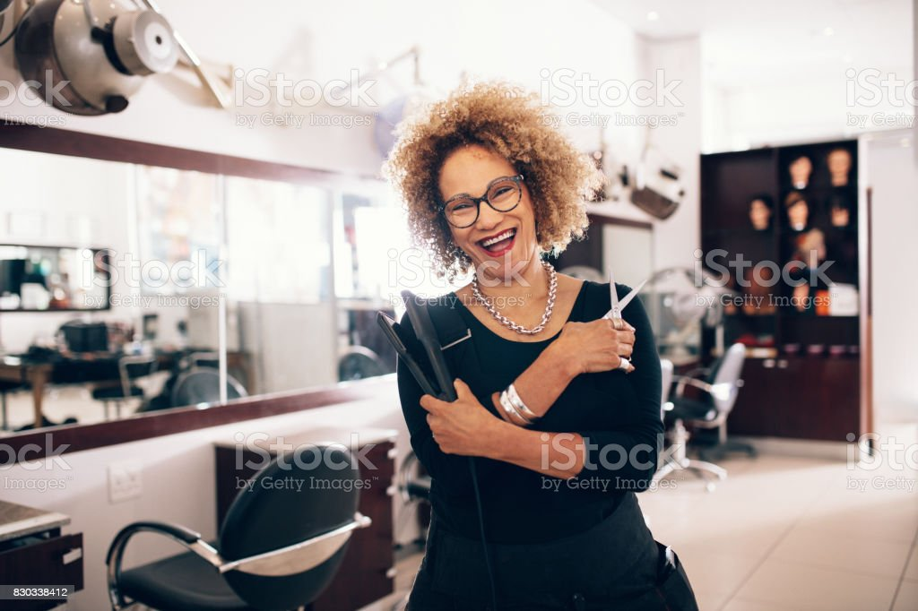 Female hairdresser at the salon holding hairdressing tools stock photo
