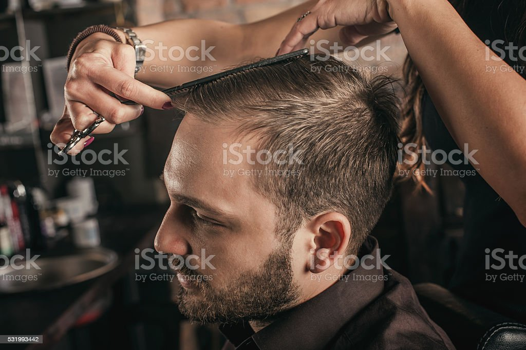 Female hairdresser hairstyle hair of man stock photo