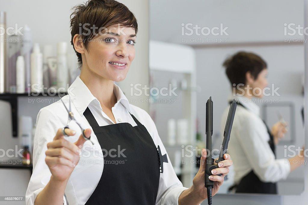 Female hairdresser holding scissors and hair straightener royalty-free stock photo